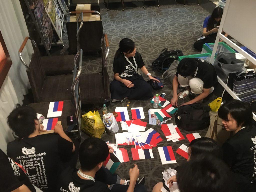 おもてなし学生が代表をおもてなしをするため国旗を制作中